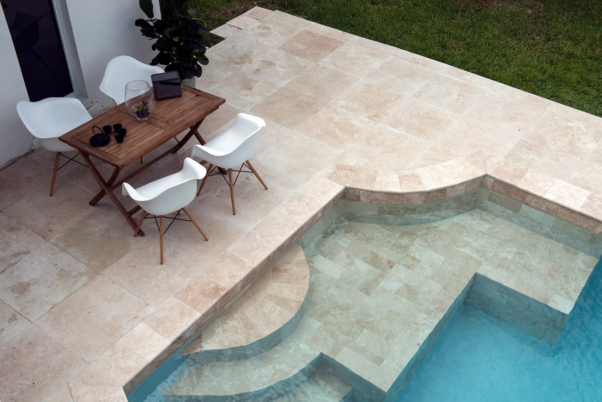 ivory travertine pavers and ivory pool coping installed around a pool