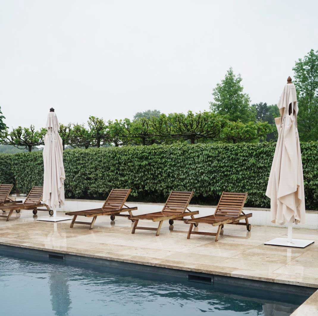 24x36 Ivory Swirl Travertine Pavers installed around a pool with chairs and umbrellas on a rainy day