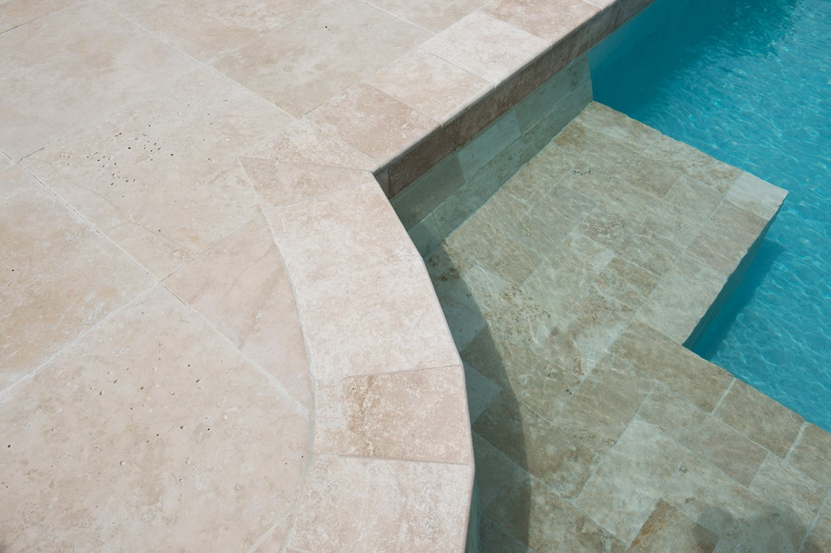 12x12 ivory travertine pool coping installed on a pool edge
