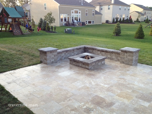 A travertine retaining wall and fire pit will add beauty and value to your home.